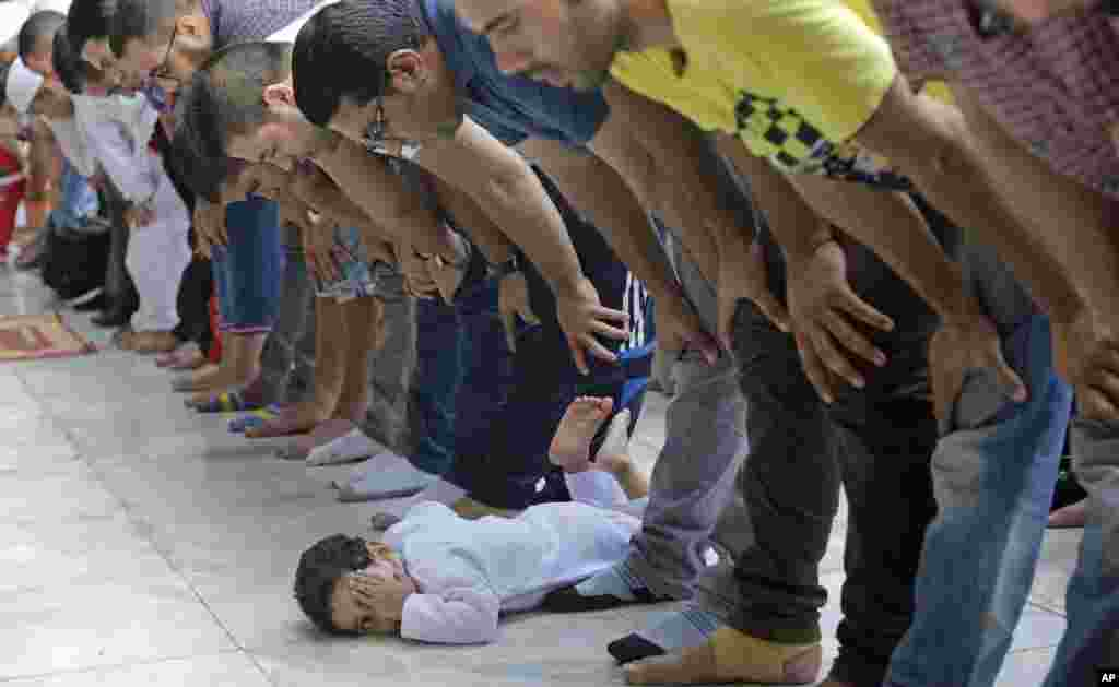 An Egyptian child plays as Muslims pray Eid al-Fitr prayers, marking the end of the Muslim holy fasting month of Ramadan at Al-Azhar mosque, the highest Islamic Sunni institution, in Cairo.