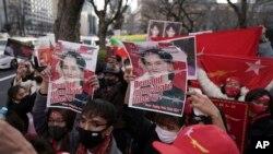 Warga Myanmar yang tinggal di Jepang dan pendukungnya memegang foto pemimpin Myanmar Aung San Suu Kyi saat melakukan protes di depan Kementerian Luar Negeri di Tokyo, Rabu, 3 Februari 2021. (Foto: AP)