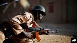 ທະຫານຂອງມາລີຜູ້ນຶ່ງ ລີ້ບັງຢູ່ຫລັງລົດໃຫຍ່ ໃນຂະນະທີ່ ຍິງຕໍ່ສູ້ຕອບກັນກັບ ພວກຈີຮາດ ທີ່ເມືອງ Gao ທາງພາກເໜືອ ຂອງ Mali ໃນວັນອາທິດ ທີ 10 ກຸມພາ 2013.