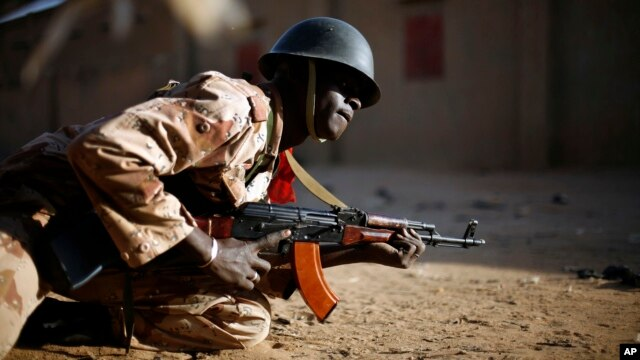 A Malian soldier takes cover behind a truck during exchanges of fire with jihadists in Gao, northern Mali, Sunday, Feb. 10, 2013.