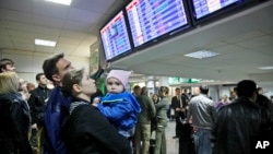 FILE - Travelers check a departures board at Borispol International Airport, near Kyiv, Ukraine.