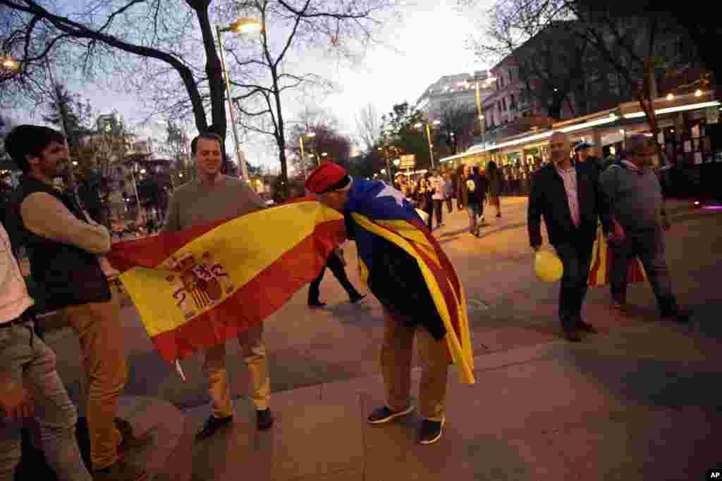 یکی از طرفداران استقلال کاتالونیا از اسپانیا، در حالیکه پرچم کاتالونیا را روی دوش انداخته است بر پرچم اسپانیا بوسه میزند. شنبه شب طرفداران استقلال کاتالونیا در مادرید تظاهرات کردند. مخالفان استقلال کاتالونیا نیز همزمان در خیابان ها حضور داشتند.
