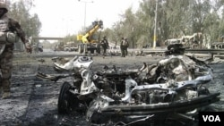 Bangkai mobil yang hancur akibat serangan dua bom mobil di dekat Zona Hijau, Baghdad, Senin (18/4).