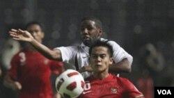 Muhamad Roby (depan) berebut bola dengan pemain Qatar, Khalfan Ibrahim, pada pertandingan Selasa malam (11/10) di Gelora Bung Karno, Jakarta.