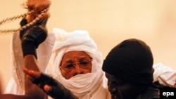 L'ancien président tchadien Hissène Habré se débat, tenu par deux gendarmes, lors d'une comparution au Palais de Justice à Dakar, Sénégal, 20 juillet 2015.