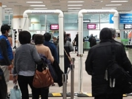 Passengers from Japan passing through a radiation screening point at Gimpo International Airport, Sunday, 27 March 2011