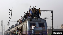 Passengers travel on an overcrowded train on the outskirts of New Delhi February 26, 2015. India will increase investment in its overloaded railway network to 8.5 trillion rupees ($137 billion) over the next five years, the government said on Thursday, pr