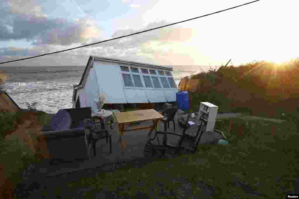 Furniture sits in the garden of a house that fell into the sea during a storm surge in Hemsby, eastern England, Britain.