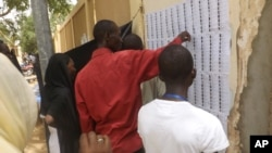 Voters look for their names before casting their ballots during elections in N'Djamena, Chad, Sunday, April 10, 2016.