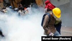 Para demonstran anti-pemerintah berjalan menghindari gas airmata yang ditembakkan untuk membubarkan mereka, dalam peringatan setahun protes anti-pemerintah di pusat kota Istanbul (31/5).