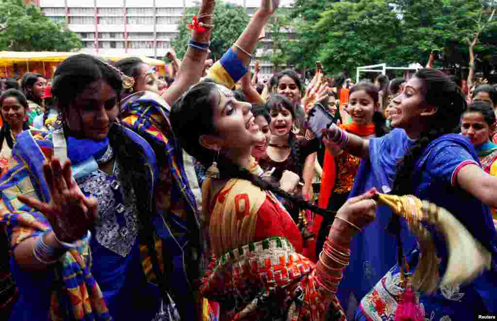 "Traditionally dressed girls dance as they celebrate the ""Teej"" festival, which falls in the Hindu holy month of Shravan (July-August) and welcomes the advent of the monsoon in Chandigarh, India."