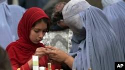 هرات، یوه افغانه مور او لور په یوه دوکان کې د سینگار شیان اخلي.