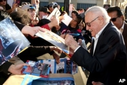 "Comic-book writer Stan Lee signs autographs as he arrives at the Los Angeles premiere of ""Captain America: Civil War"" at the Dolby Theatre, April 12, 2016."