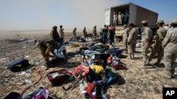 Des soldats égyptiens récupérant les effets personnels des victimes du crash, à Hassana, le 2 novembre 2015.