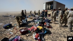 Egyptian soldiers collect personal belongings of plane crash victims at the crash site of a passenger plane bound for St. Petersburg in Russia that crashed in Hassana, Egypt's Sinai Peninsula, Nov. 2, 2015.