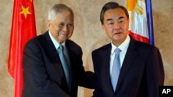 Chinese Foreign Minster Wang Yi (R) is greeted by Philippine Foreign Secretary Albert Del Rosario upon arrival at the Department of Foreign Affairs, Nov. 10, 2015, at suburban Pasay city, south of Manila, Philippines.