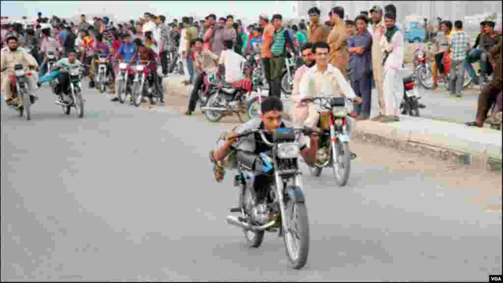 لیٹ کر موٹر سائیکل چلاتا ہوا ایک نوجوان، تماشائی بھی نمایاں ہیں