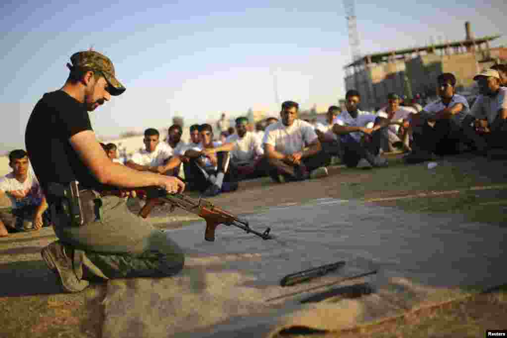 Shi'ite volunteers from the Supreme Islamic Iraqi Council watch a man handle a weapon during a training in Najaf, June 24, 2014. U.S. Secretary of State John Kerry held crisis talks with leaders of Iraq's autonomous Kurdish region on Tuesday urging them t