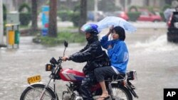 Man struggles to ride motorcycle carrying a woman during heavy rain brought by Typhoon Nesat in Qionghai, Hainan province September 29, 2011