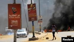 Para pengendara melintas di depan ban-ban yang dibakar sebagai penghalang di tengah demonstrasi untuk mendesak pemerintah memperbaiki kondisi negara di Khartoum, Sudan, Rabu, 21 Oktober 2020. (Foto: Reuters)