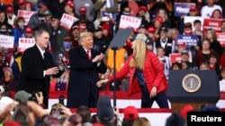 U.S. President Donald Trump applauds as he hosts a campaign event with U.S. Republican Senators David Perdue (L) and Kelly Loeffler (R) at Valdosta Regional Airport in Valdosta, Georgia, U.S., December 5, 2020.