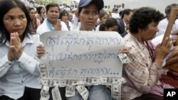 "A Cambodian supporter holds a banner reading: ""The court system must be respected by the public not for..."" as she sits with other supporters of Mam Sonando, one of Cambodia's most prominent human rights defenders, in front of Phnom Penh Municipal Court in Phnom Penh, Cambodia, Tuesday, Sept. 11, 2012. Some 300 supporters gathered for prayer for local radio station owner Sonando, who has been held in pre-trial detention for almost two months for insurrection charge, during his court appearance. (AP Photo/Heng Sinith)"