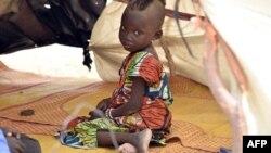 Un enfant assis dans une tente dans un camp au village de Kidjendi, près Diffa, le 19 juin 2016 après que des familles ont fui les attaques menées par Boko Haram à Bosso.