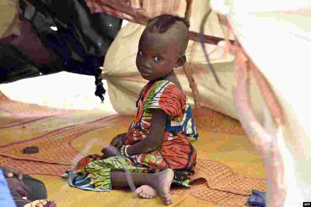 A child looks on under a makeshift tent in a camp in the village of Kidjendi near Diffa as displaced families fled from Boko Haram attacks in Bosso, Niger.