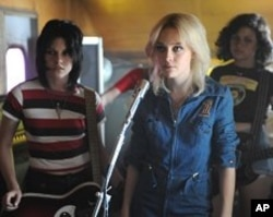 "Joan Jett (Kristan Stewart), Cherie Currie (Dakota Fanning), and Robin (Alia Shawkat) practice in ""The Runaways"""