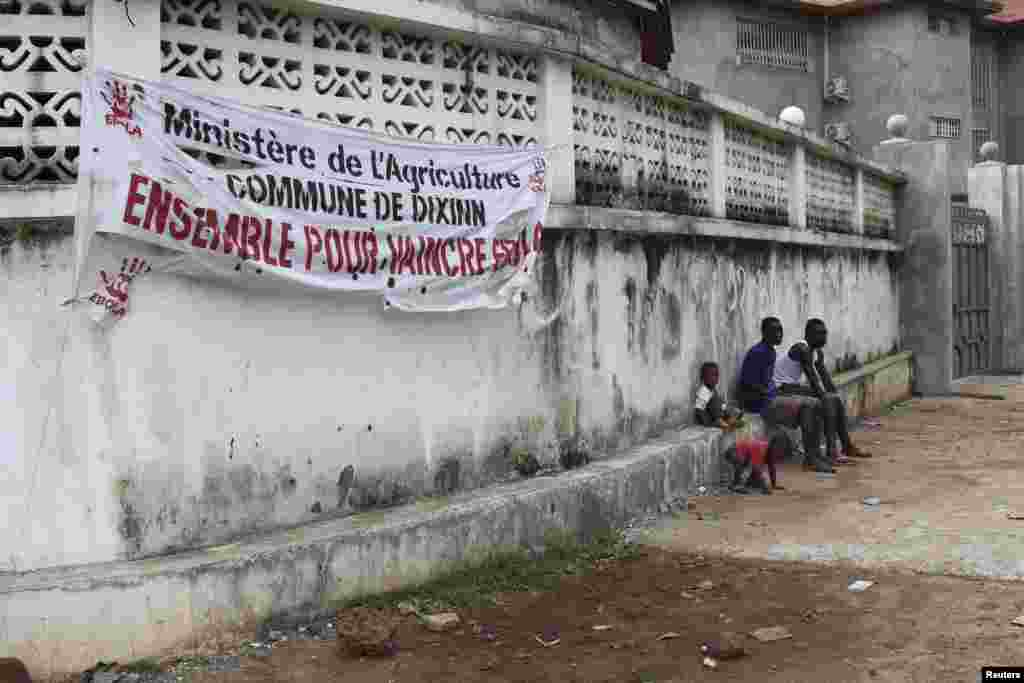 """People sit near a banner reading """"The Ministry of Agriculture, Dixinn Commune, Together to defeat Ebola,"""" in Conakry, Guinea, Oct. 26, 2014."""