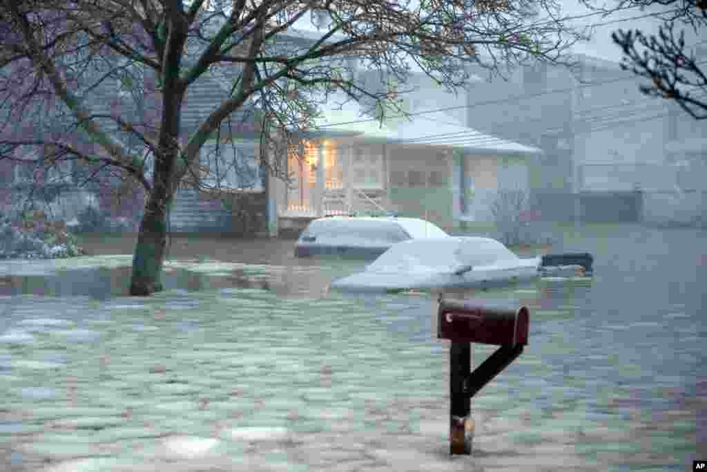 Water floods a street on the coast in Scituate, Massachusetts, Jan. 27, 2015. A storm packing blizzard conditions spun up the East Coast, pounding parts of coastal New Jersey northward through Maine with high winds and heavy snow.