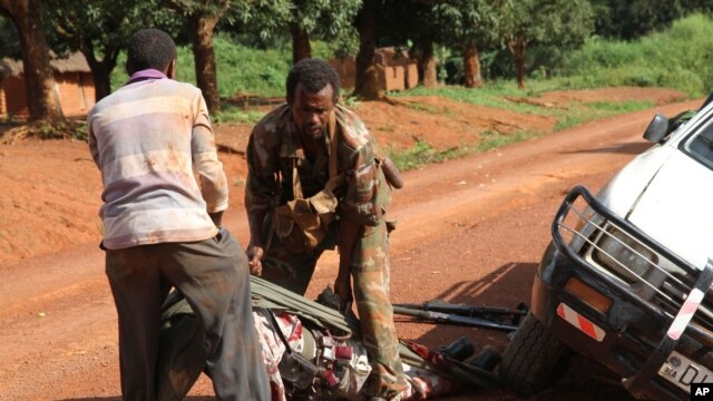 In this Sept. 16, 2013 photo, A Gabonese soldier from a regional Central African peacekeeping force helps collect the bodies of rebels who were reportedly killed by armed villagers in Njoh, Central African Republic.