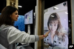 Chloe Szulzinger demonstrates on CareOS, an operating system that connects multiple devices in the bathroom, during CES Unveiled at CES International Sunday, Jan. 7, 2018, in Las Vegas. (AP Photo/Jae C. Hong)