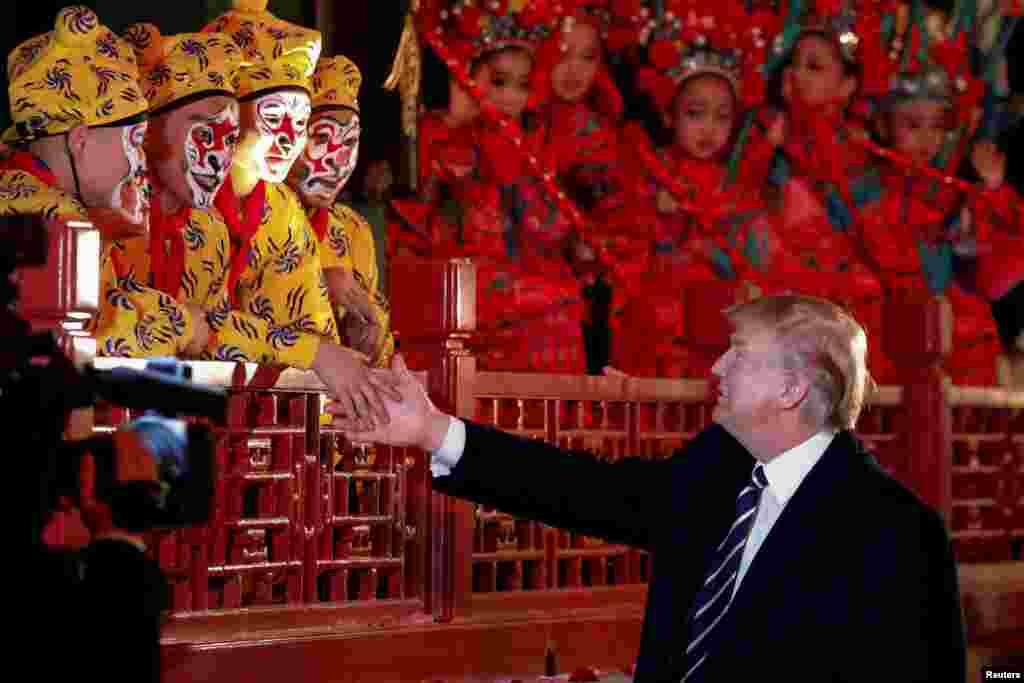 President Donald Trump shakes hands with opera performers at the Forbidden City in Beijing, China, Nov. 8, 2017.