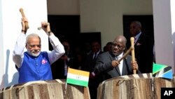 Waziri Mkuu wa India Narendra Modi, kushoto, na mwenyeji wake Rais John Pombe Magufuli, right, beat drums at the entrance of State House during an official welcome ceremony for Modi in Dar es Salaam Tanzania, July 10, 2016.