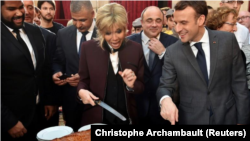 El presidente francés, Emmanuel Macron, y su esposa Brigitte cortan porciones de un tradicional pastel gigante durante una ceremonia en el Palacio del Elíseo en París, Francia, 12 de enero del 2018.