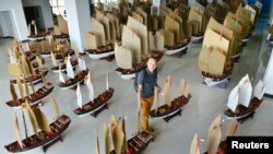 Planner and explorer Jin Feibao poses for pictures with his models of the full fleet led by Ming Dynasty eunuch explorer Cheng Ho, also known as Zheng He, in Kunming, Yunnan province, July 11, 2014.