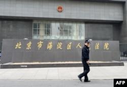 一名警察走过正在审理中国反腐败活动人士丁家喜的北京市海淀区人民法院。(2014年4月8日)