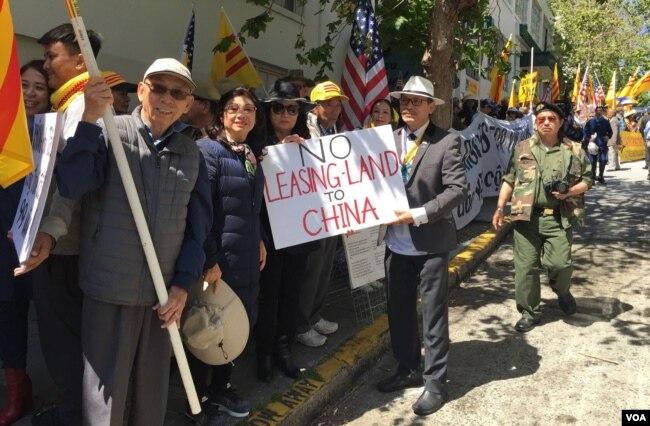 """Nghị viên Tâm Nguyễn của thành phố San Jose cùng tấm bảng có dòng chữ """"không cho Trung Quốc thuê đất""""."""