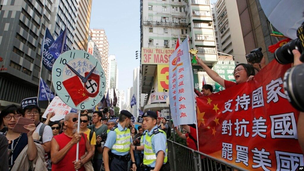 """2018年10月1日,香港两派游行集会,有人主张""""支持国家,对抗美国,罢买美国"""",也有人主张香港独立或""""为法西斯强国送终""""。"""