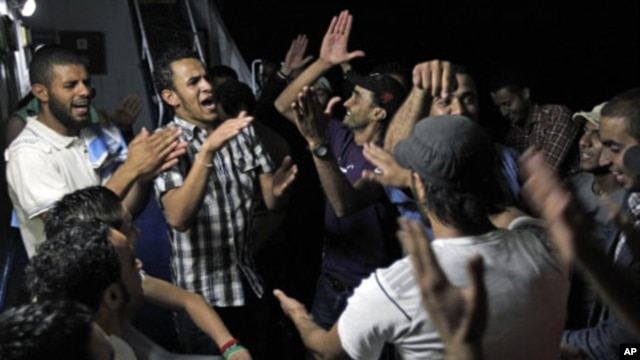 Libyans chant anti-Moammar Gadhafi slogans aboard the Azzurra Line on their way from Benghazi to Misratah, Libya. Bombing continued early Friday as three fresh strikes sent plumes of smoke over Tripoli, June 10, 2011