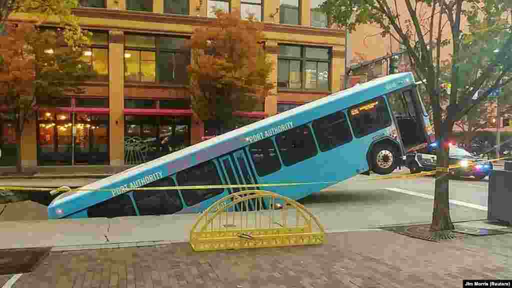 Front of a public bus sticks out of a sinkhole on 10th and Penn Avenue in Pittsburgh, Pennsylvania, in this picture obtained from social media.