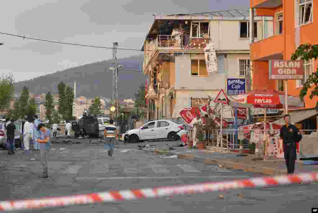 Turkish police officers work near the site of an explosion at a police station, seen right, in Istanbul's Sultanbeyli neighborhood, early Monday, Aug. 10, 2015.