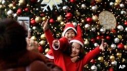 身穿圣诞老人服装的母子二人在北京一家商场的圣诞树前合影。(2017年12月25日)