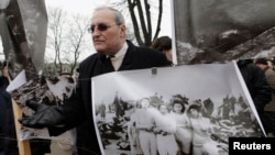 FILE - Holocaust historian Efraim Zuroff stands beside a poster showing victims of Nazi war crimes, in Riga, Latvia, March 16, 2012.