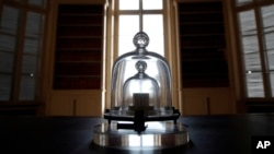 In this photo taken Wednesday, Oct. 17, 2018., a replica of the International Prototype Kilogram is pictured at the International Bureau of Weights and Measures, in Sevres, near Paris. (AP Photo/Christophe Ena)