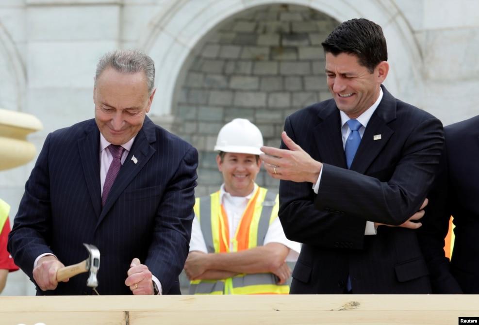 미국 워싱턴 DC의 연방 의사당 주변환경 개선 공사 현장에 나온 척 슈머(민주·뉴욕) 상원의원이 못질하는 모습을 보고 폴 라이언(공화·위스콘신) 하원의장이 웃음을 터뜨리고 있다.