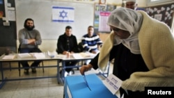 A Druze woman casts her ballot for the parliamentary election at a polling station in the northern Druze-Arab village of Maghar, Israel, January 22, 2013.