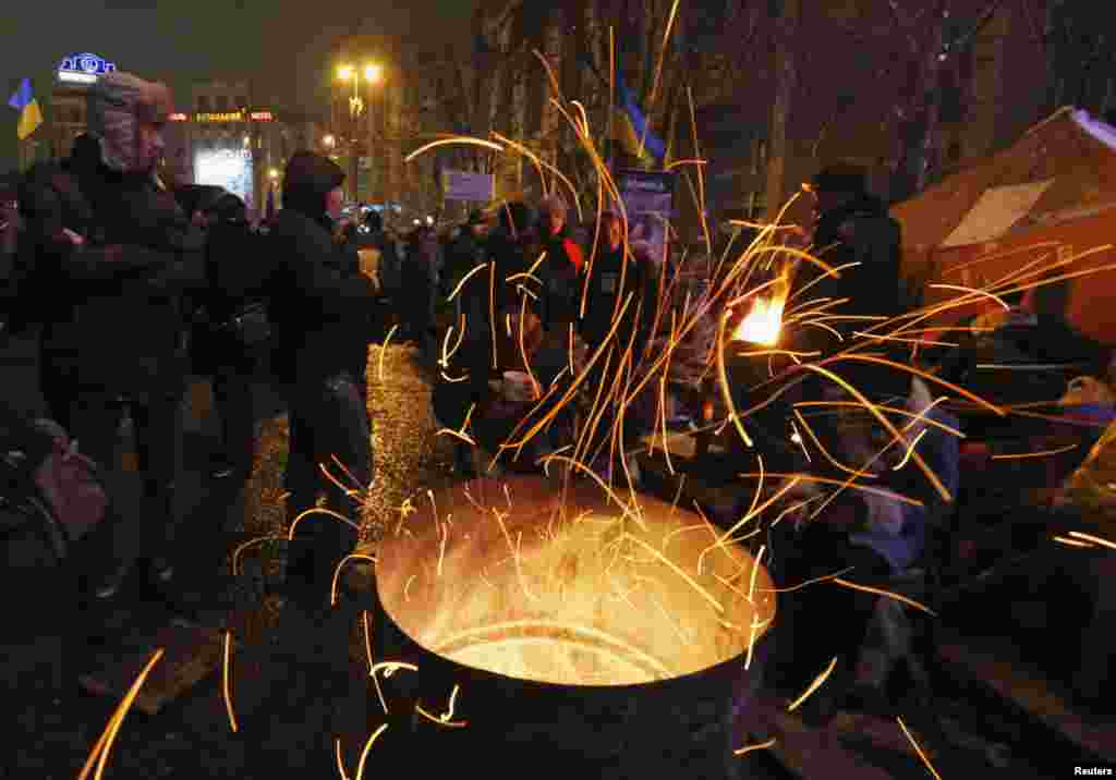 Pro-European integration protesters warm themselves by a fire in Independence Square in Kyiv, Dec. 12, 2013.