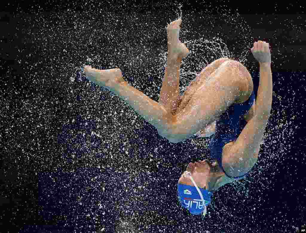 A member of the Italy team is thrown up in the air during a synchronized swimming training session ahead of the FINA Swimming World Championships in Barcelona, Spain, July 18, 2013.